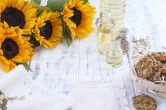 Solrosolja och stora gula blommor Olja i buteljera Utan peelen av solrosfrö och kakor vitt trä för bakgrund Royaltyfri Foto