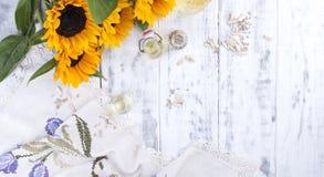 Solrosolja och stora gula blommor Olja i buteljera Utan skal av solrosfrö vitt trä för bakgrund Tappning Arkivbild