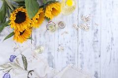 Solrosolja och stora gula blommor Olja i buteljera Utan skal av solrosfrö vitt trä för bakgrund Tappning Royaltyfria Bilder