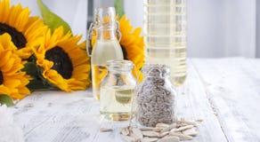 Solrosolja och stora gula blommor Olja i buteljera Utan skal av solrosfrö vitt trä för bakgrund Tappning Arkivfoto
