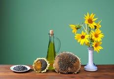 Solrosor i en vas och en olja Arkivbild