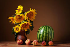 Solrosor i en vas och en vattenmelon Arkivfoton
