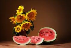Solrosor i en vas och en vattenmelon Royaltyfri Foto