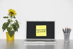 Solrosväxten på skrivbordet och klibbig brevpapper med fransk text på bärbar datorskärmen som säger förbipasseranden le, arbetar t Arkivbild