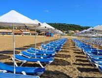 Solsängar och paraplyer på en sandig strand Arkivfoto