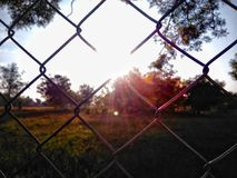 Solsken bak staketet Arkivfoto