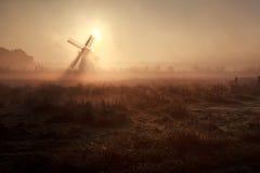 Solsken bak väderkvarnen i dimmig morgon Royaltyfri Bild