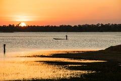 Solsken i aftonen, har fiskarerodd, solnedgångbackgrou Arkivbilder