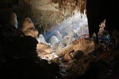 Solsken in i stalaktitgrottan Arkivbild