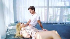 Solsken på den blonda kvinnan som ligger på varv av mannen, i solbelyst rum och samtal lager videofilmer