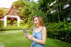 Solskenståenden av den unga kvinnan som förvånas med minnestavlan och att le på gräsplan, gömma i handflatan och husbakgrund i Th arkivfoton