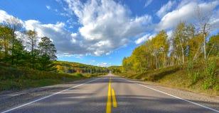 Solskenväg, enkelt punktperspektiv ner en landshuvudväg i sommar Fotografering för Bildbyråer