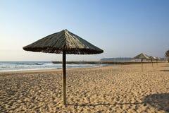 Solskuggaparaplyer uppställda på den tomma stranden Arkivfoton