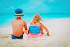 Solskyddspys och flicka med suncream p? stranden royaltyfri bild