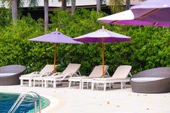 Solstol eller sunbath n?ra privat simbass?ng med solparaplyet och exotiska v?xter arbeta i tr?dg?rden, semestrar och semestrar be arkivfoto