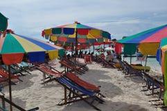 Solstolar och färgrika paraplyer på en strand Arkivbild