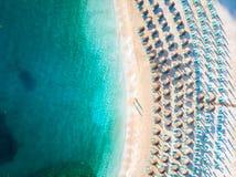 Solstolar och paraplyer sätter på land med inget turister och klart blått vatten arkivbilder