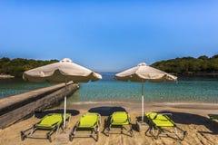 Solstolar och parasollstrandparaplyer på den guld- Ksamilen sätter på land med små öar i turkoshavet, Albanien royaltyfri fotografi