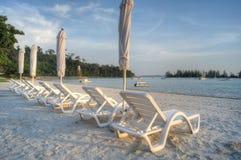 Solstolar och strandparaplyer på stranden Royaltyfri Foto