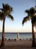 Solstolar på en strand royaltyfria bilder