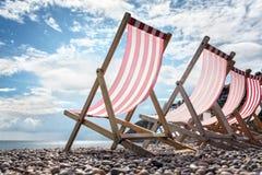 Solstolar på stranden på sjösidasommarsemestern Royaltyfri Foto
