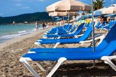 Solstolar över sanden i en idyllisk strand i Ibiza som är balearic Arkivbilder