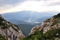 Solstrålar över berg Arkivfoton