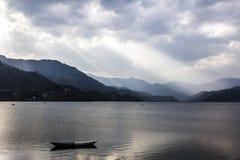 Solstrålar över Pokhara sjön Arkivfoto