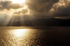Solstrålar över Sicilien som ses från Calabria Royaltyfri Fotografi