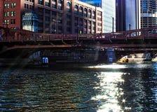 Solstrålar fördjupa över den i stadens centrum Chicago öglan som skapar blänka stjärnor på floden under morgon royaltyfri bild