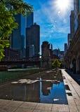 Solstrålar fördjupa över färgstänkblocket med reflexioner av cityscape på Chicago River går i i stadens centrum ögla arkivfoto