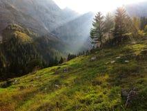 Solstrålar in i bergdalen på nedgången Royaltyfri Fotografi