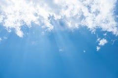 Solstrålar med bakgrunden för blå himmel Arkivbild