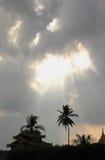 Solstrålar och mörker fördunklar över palmträd Royaltyfri Foto