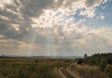 Solstrålar och moln Arkivbild