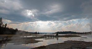 Solstrålar och ovannämnd ånga för solstrålar som stiger av den varma sjön i den lägre Geyserhandfatet i den Yellowstone nationalp Royaltyfri Foto