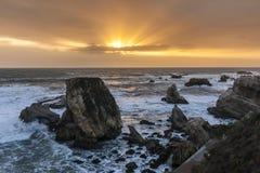Solstrålar och Rocky Beach Arkivfoto