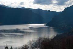 Solstrålar på Idro sjön mellan berg arkivbild