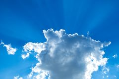 Solstrålar som bryter till och med ett stackmolnmoln royaltyfri fotografi
