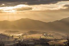 Solstrålar som kommer över en dal i Umbria Italy arkivbilder