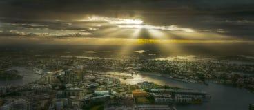 Solstrålar som skiner över stad Royaltyfria Foton