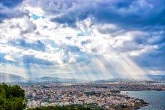 Solstrålar som skiner till och med de dramatiska molnen över staden Chania Arkivbild