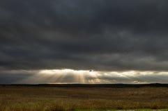 Solstrålar till och med mörka moln arkivbilder