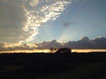 Solstrålar till och med moln Arkivbilder