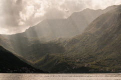 Solstrålar till och med moln på Boka-Kotorska Arkivfoto