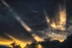 Solstrålar tränger igenom molnräkningen royaltyfria foton