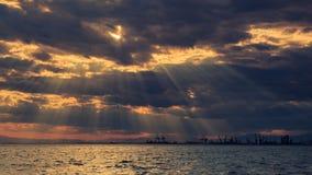 Solstråle i ljus molnig solnedgång på sjösidan som förbiser silh Royaltyfria Bilder