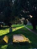 solstråle på en gravsten i den gamla engelska kyrkogården arkivbilder
