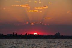 Solstråle på soluppgång över staden på havet Arkivbild