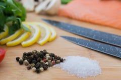Solt en peppar på skärbräda med tomaten, persilja och kniv och rå salamon Fotografering för Bildbyråer